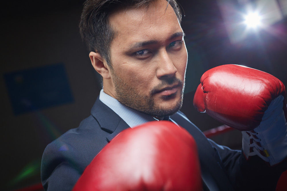 Asian Businessman In Red Boxing Gloves Looking At Camera
