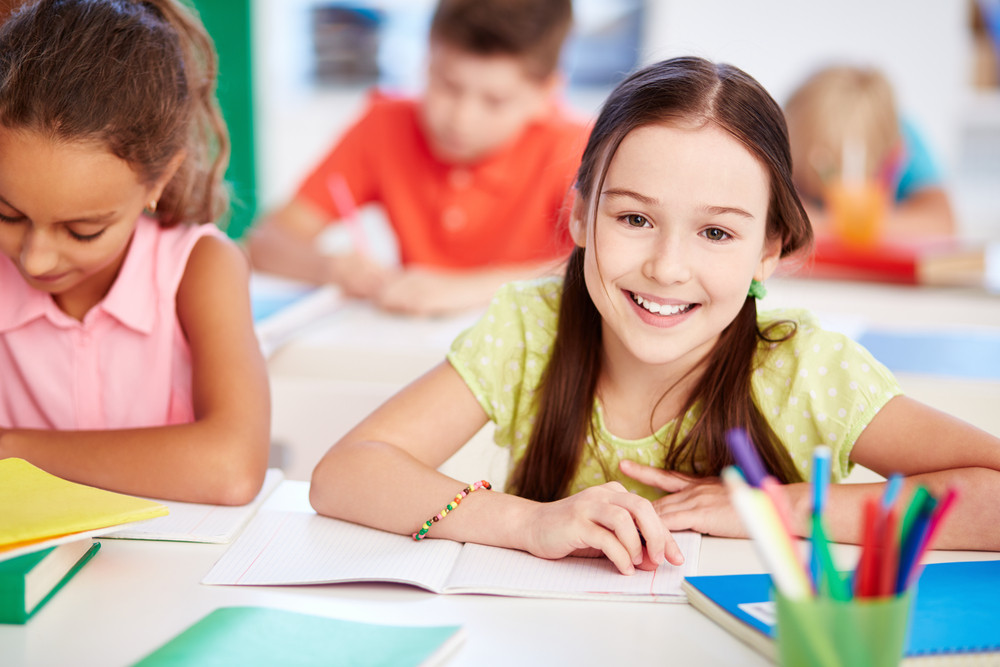 Happy Little Girl Looking At Camera At Lesson With Her Friend Near By