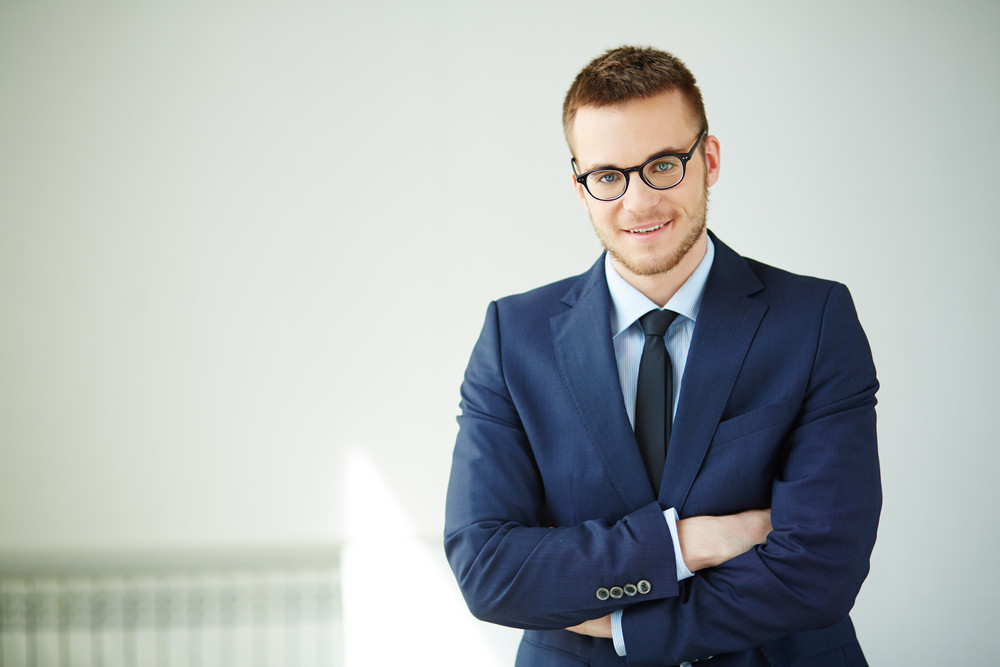 Portrait Of Smiling Employee Looking At Camera In Isolation