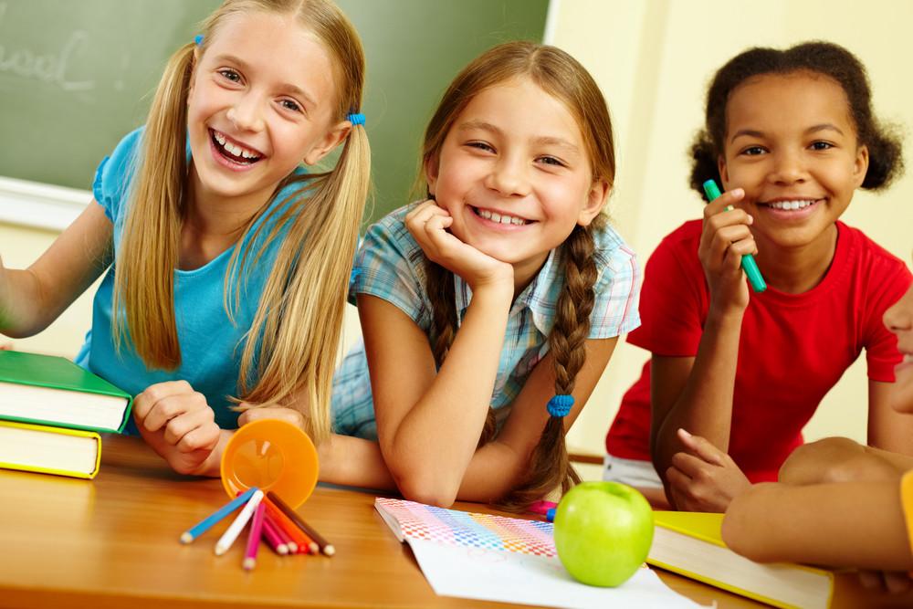 Portrait Of Joyful Schoolgirls Laughing In Classroom