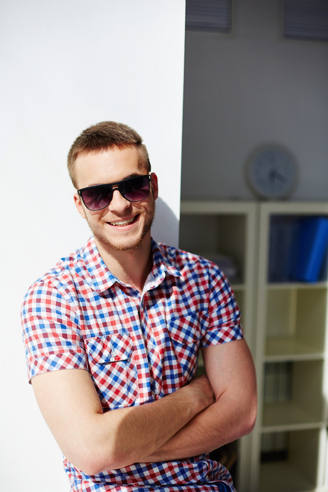 Young Guy In Sunglasses Smiling And Looking At Camera
