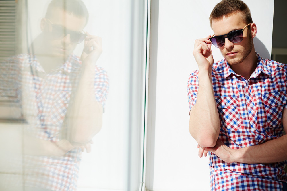 Young Guy In Sunglasses By The Window