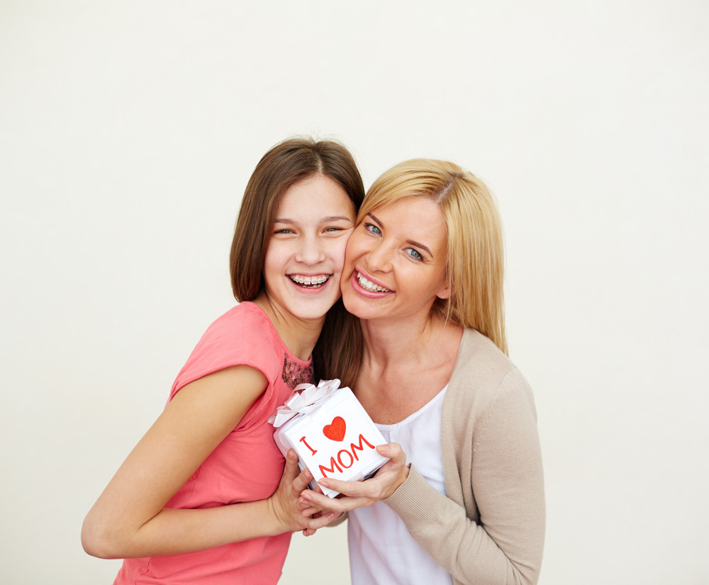 Teenage Girl And Her Mom With Small Present Looking At Camera And Laughing