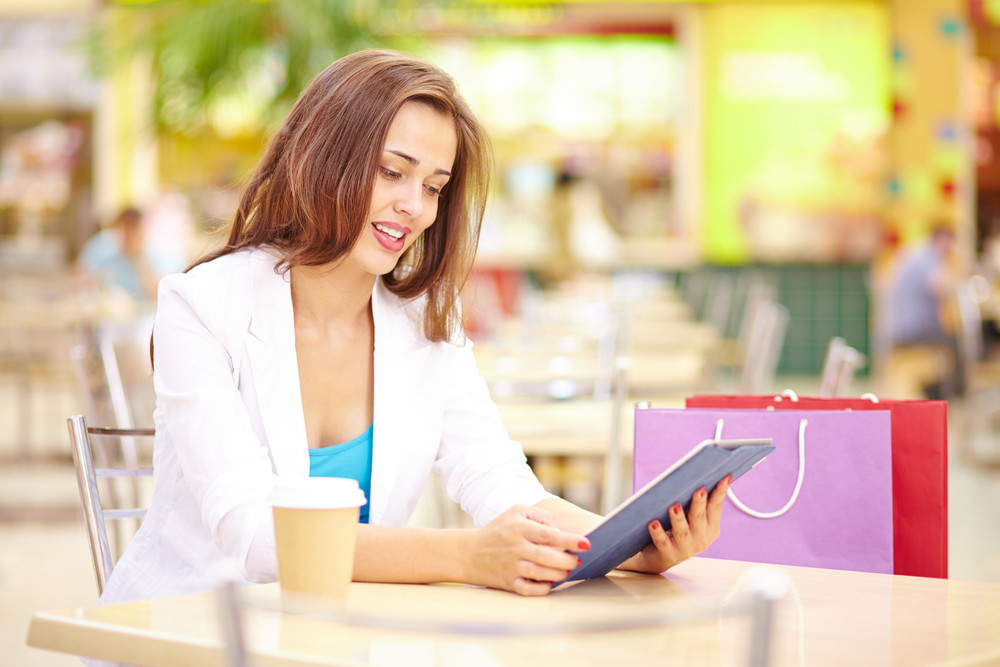 Shopping Girl Using Touchpad While Sitting In Cafe After Shopping