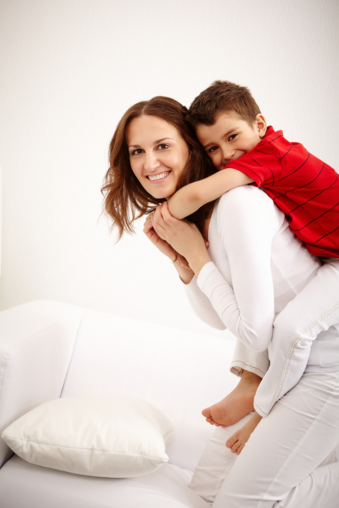 Joyful Toddler On Back Of His Mother