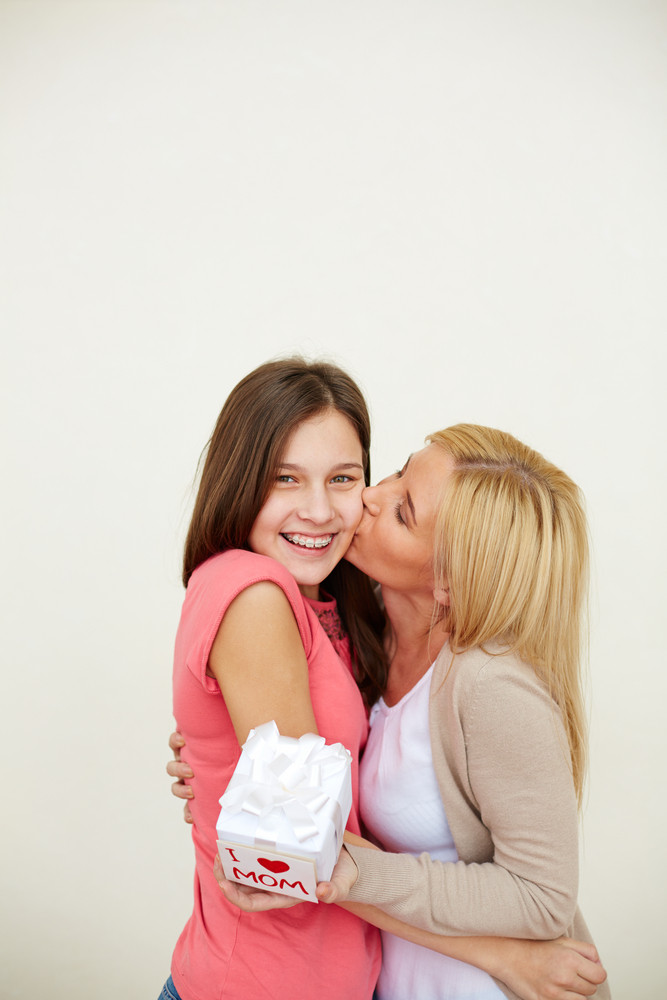 Thankful Woman With Small Present Kissing Her Daughter