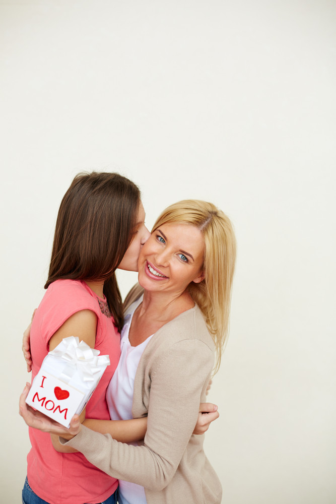 Teenage Girl Kissing Her Mom With Small Present