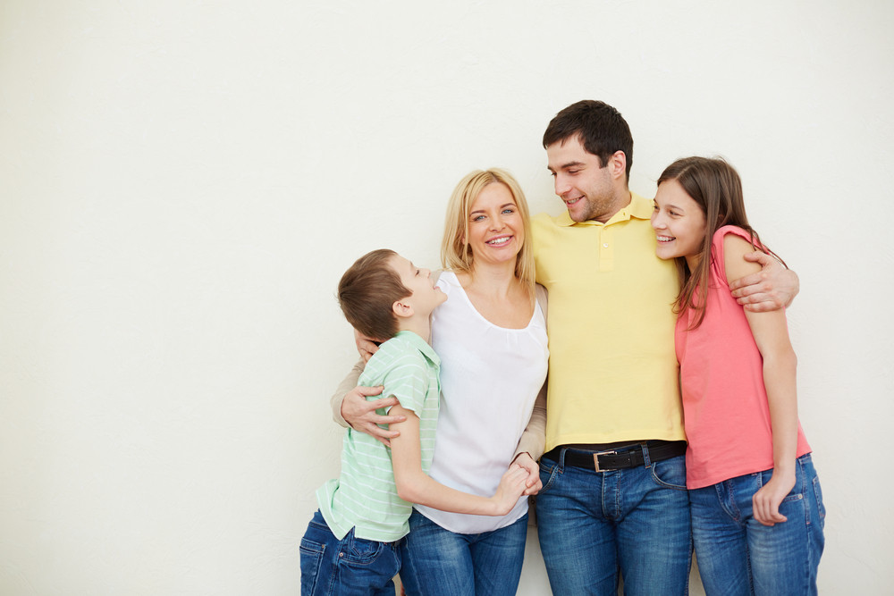 Portrait Of Affectionate Family Of Four In Isolation