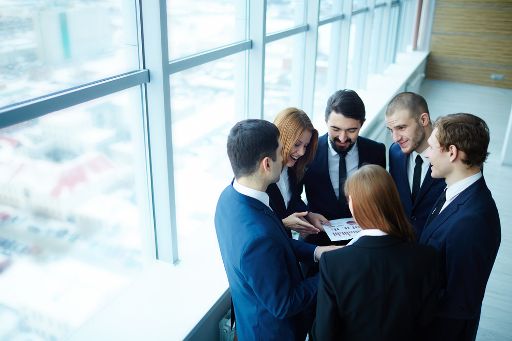 Group Of Business Partners Discussing Paper At Meeting In Office