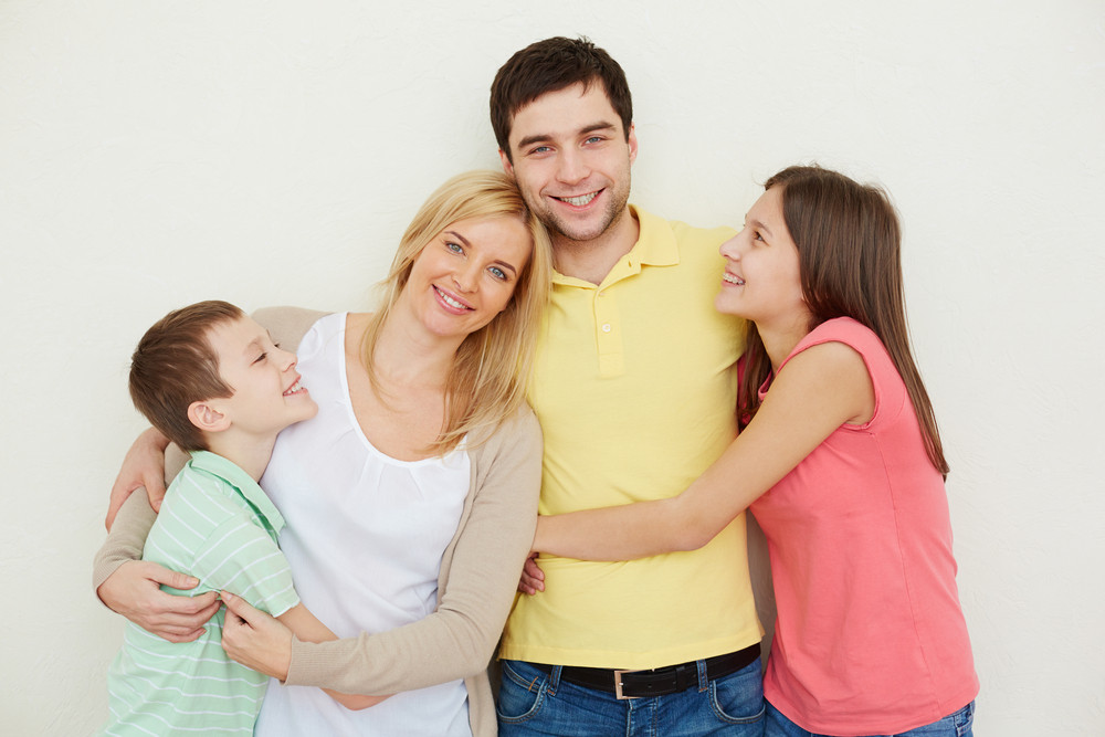 Portrait Of Affectionate Family Of Four Posing Over White Background