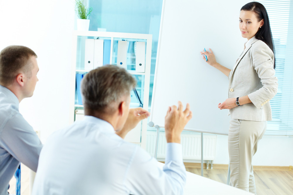 Successful Businesswoman Explaining Her Idea On Whiteboard At Office