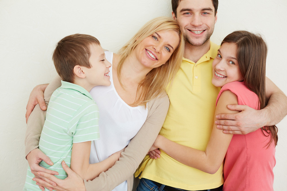 Portrait Of Affectionate Family Of Four Embracing