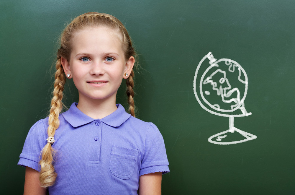 Portrait Of Smart Girl By The Blackboard Looking At Camera