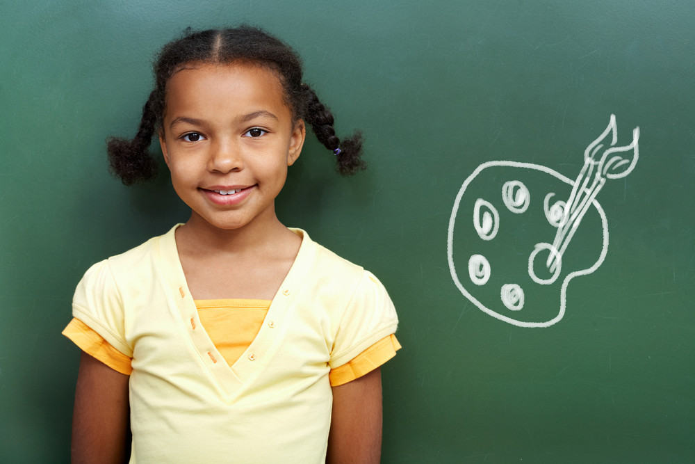 Portrait Of Cute Girl By The Blackboard Looking At Camera