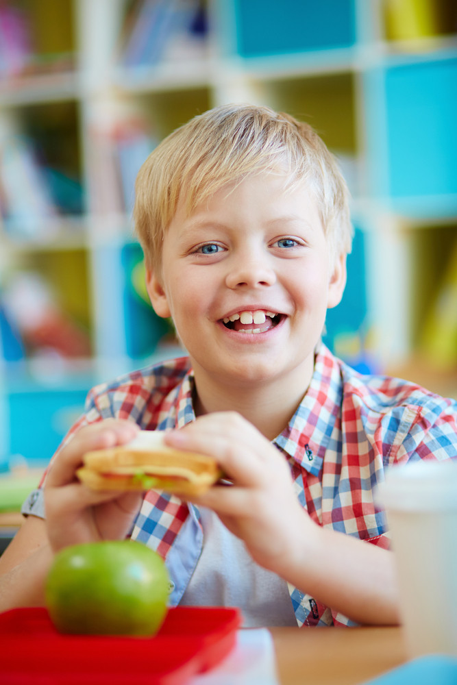 Happy Schoolboy With Sandwich Having Snack In School