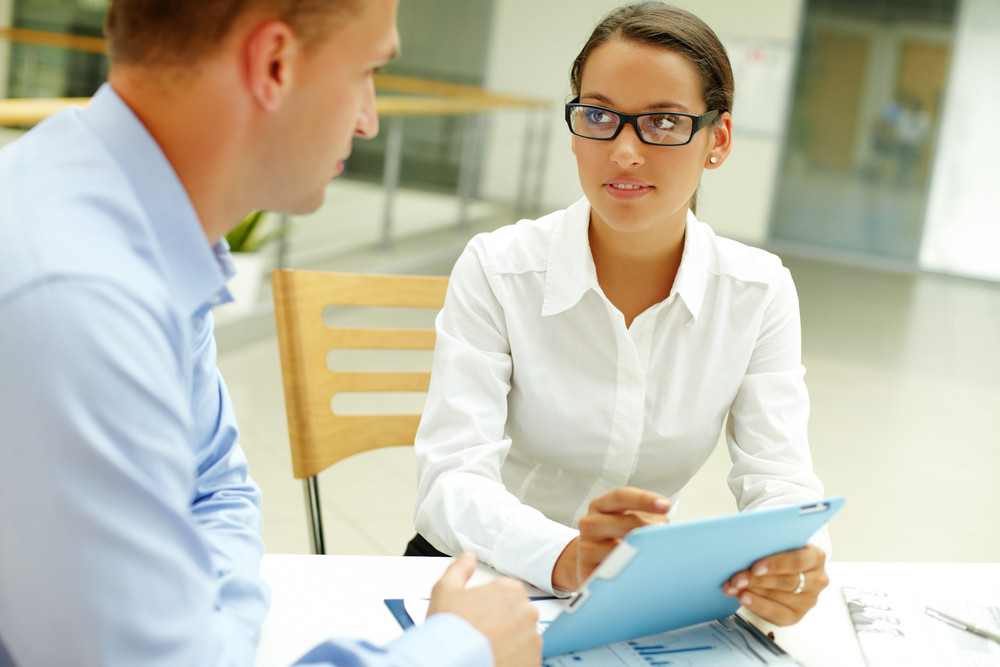 Pretty Secretary With Touchpad Looking At Young Businessman At Meeting