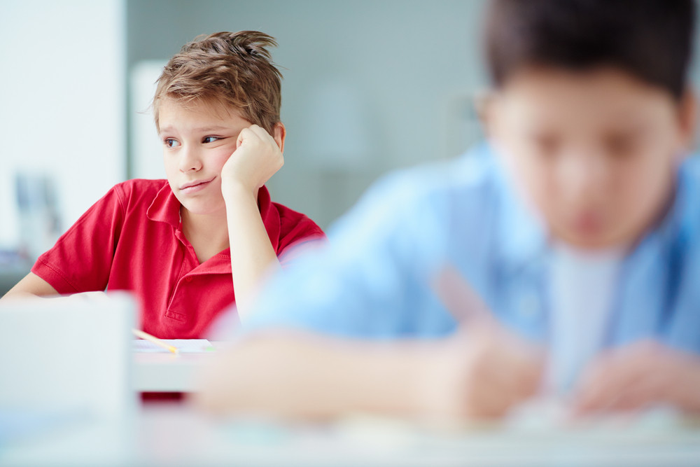 Portrait Of Bored Schoolboy Sitting At Lesson