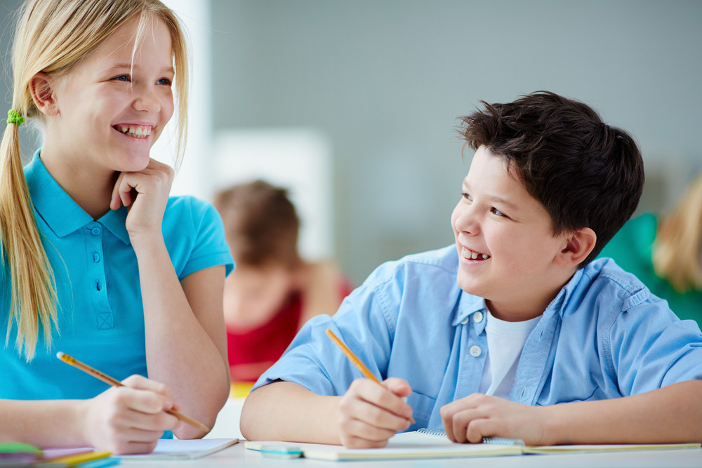Portrait Of Two Diligent Pupils Laughing While Drawing At Lesson
