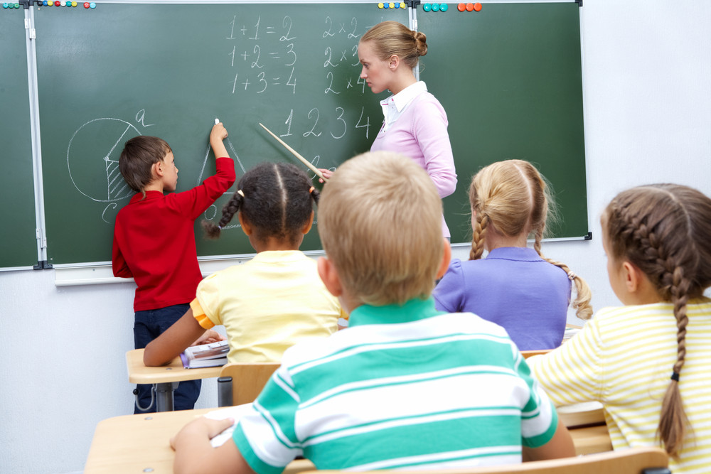 Photo Of Elementary Student By Blackboard Looking At His Teacher Helping Him