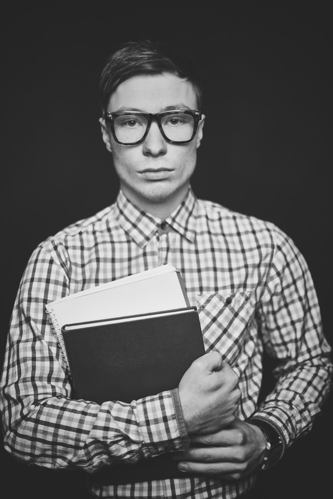 Portrait Of Serious Student With Books Looking At Camera