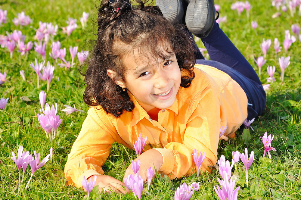 Girl on meadow with pink flowers arond