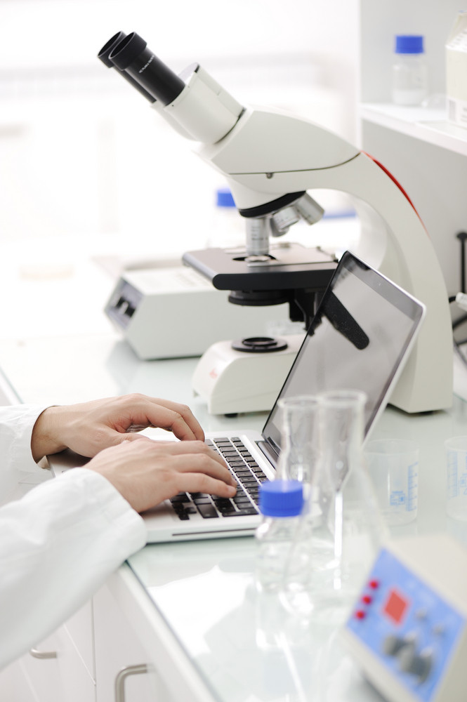 Working in lab with microscope and writing results on laptop