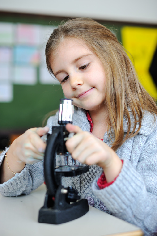 Beautiful young girl with a microscope
