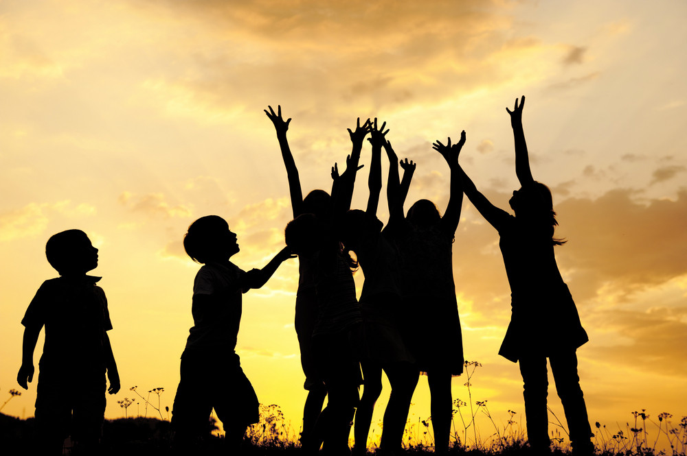Group of children silhouettes playing on nature field at sunset summertime