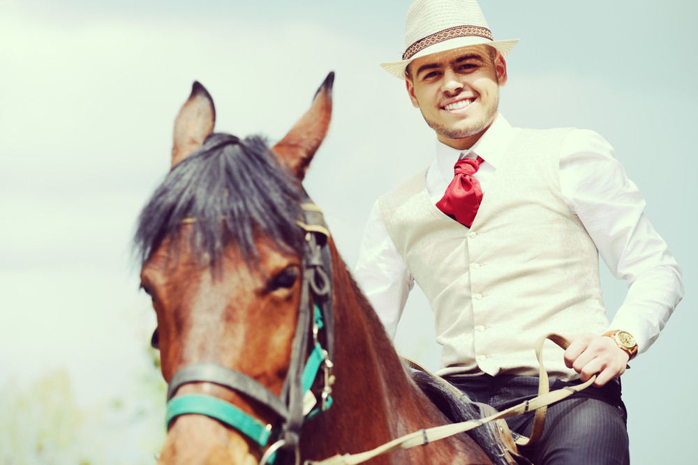 Happy young man on countryside with horse for riding