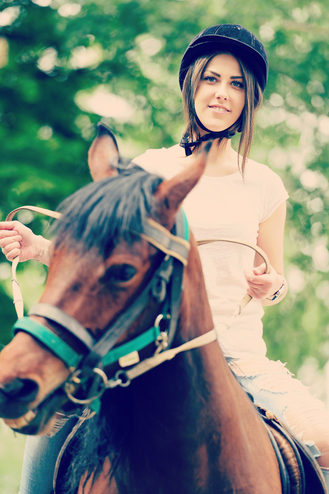 Happy young woman on countryside with horse for riding
