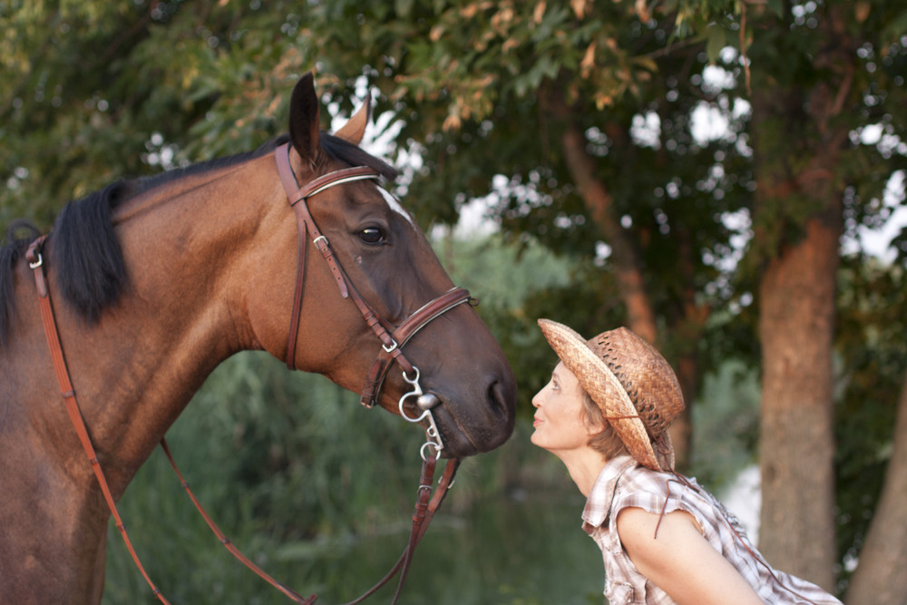 Woman in hat and horse face to face.