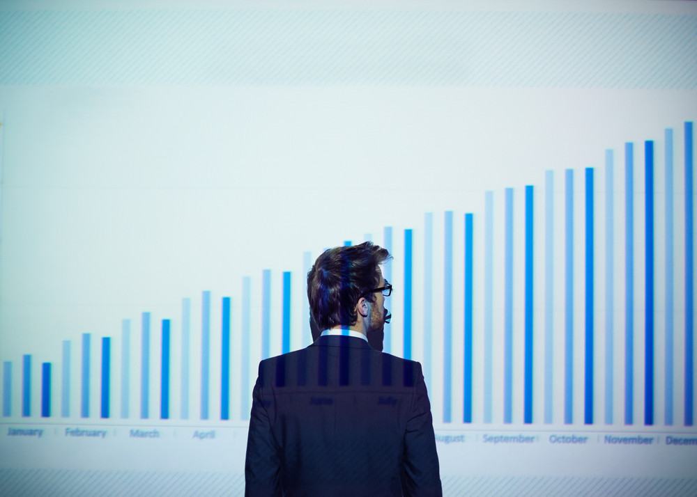 Rear View Of Businessman Standing By Wall And Looking At Chart On It