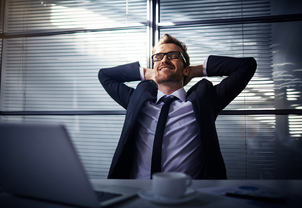 Happy Young Businessman Dreaming In Office