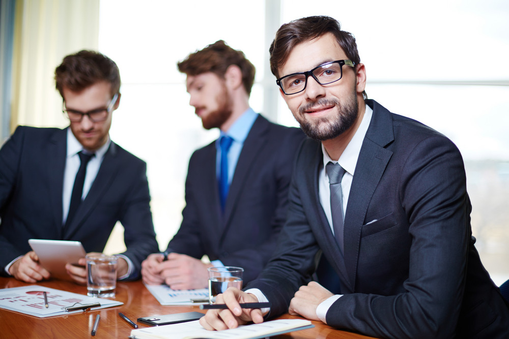 Happy Businessman Looking At Camera With Two Male Employees Communicating On Background