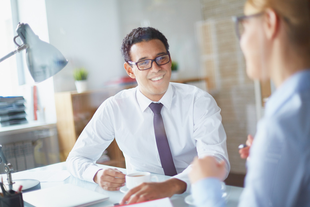 Happy Businessman Listening To His Partner At Coffee Break