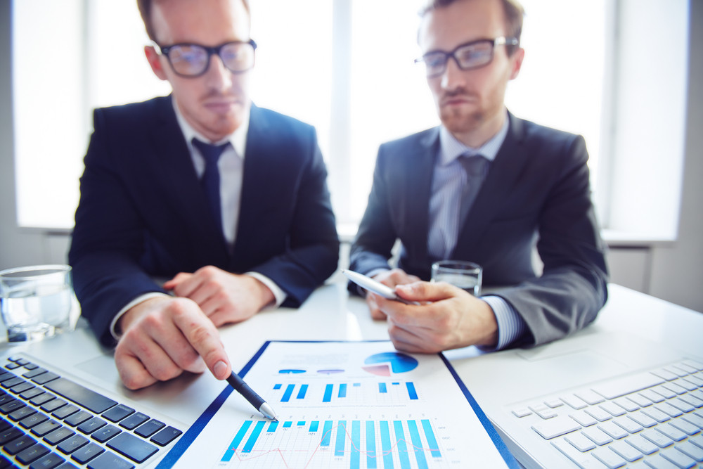 Confident Businessman Analyzing Chart And Explaining It To Co-worker