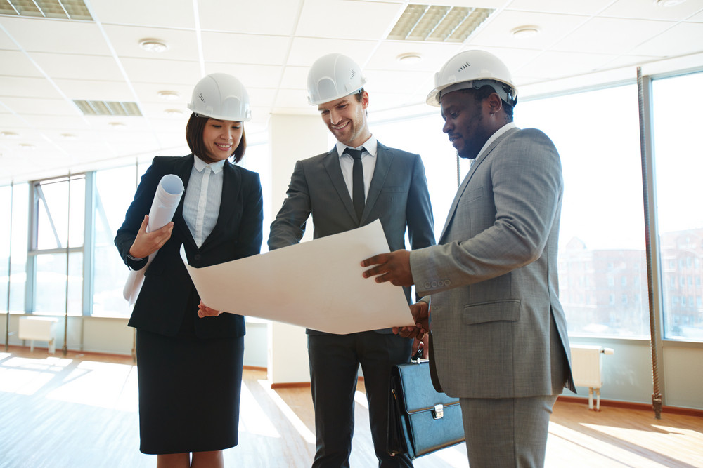Confident Architects In Protective Helmets Discussing Blueprint In Office