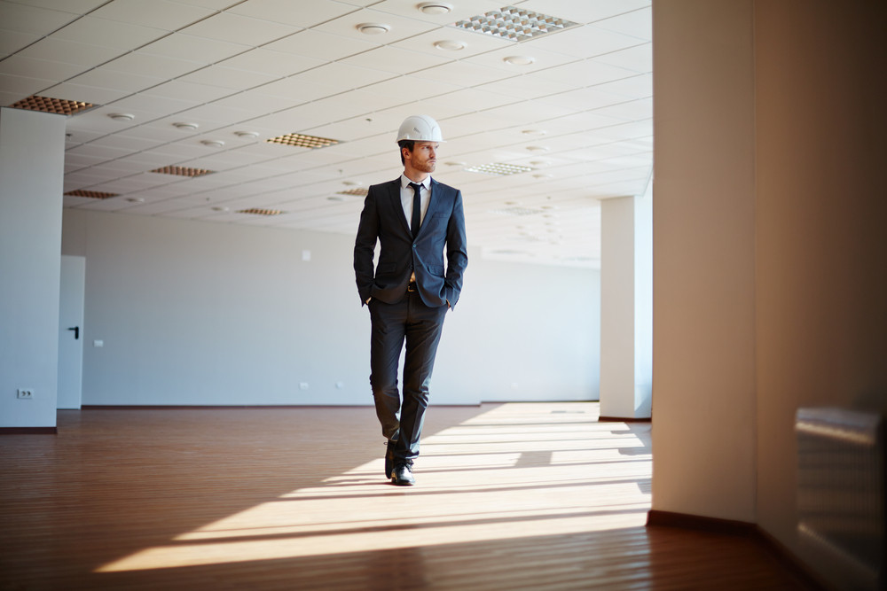 Male Architect In Suit And Helmet Walking Along Office