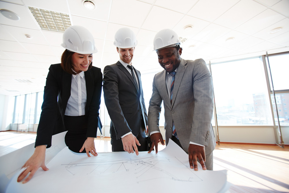 Confident Architects In Protective Helmets Looking At Blueprint
