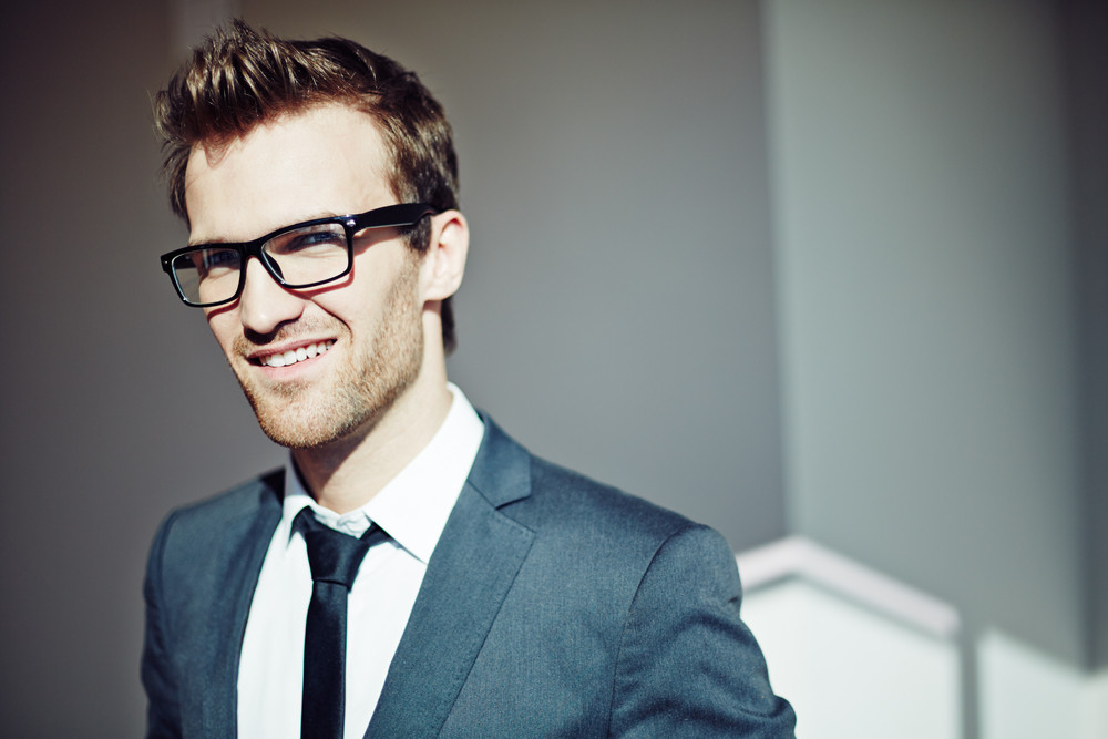 Confident Young Businessman In Eyeglasses Looking At Camera