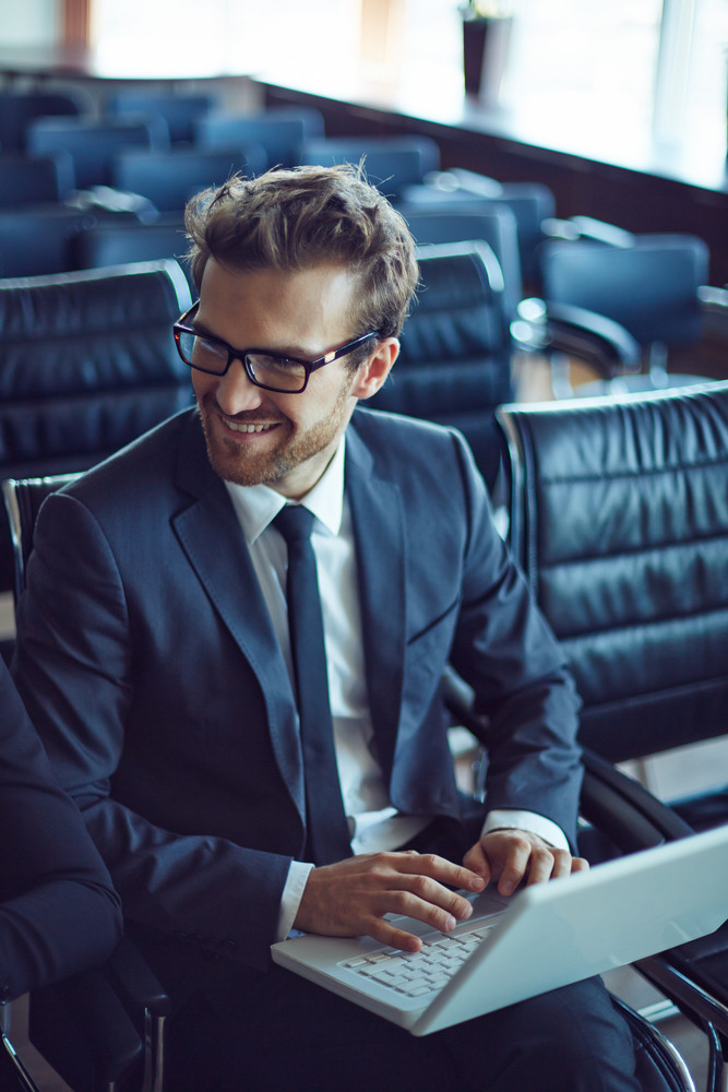 Male Employee Typing While Listening To Colleague At Meeting