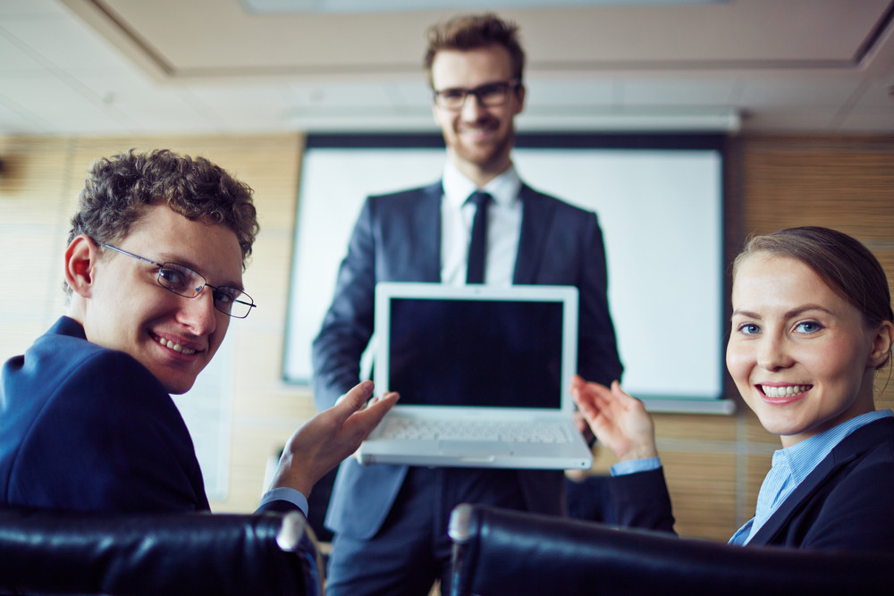 Happy Business Partners Looking At Camera While Pointing At Laptop Display Held By Man