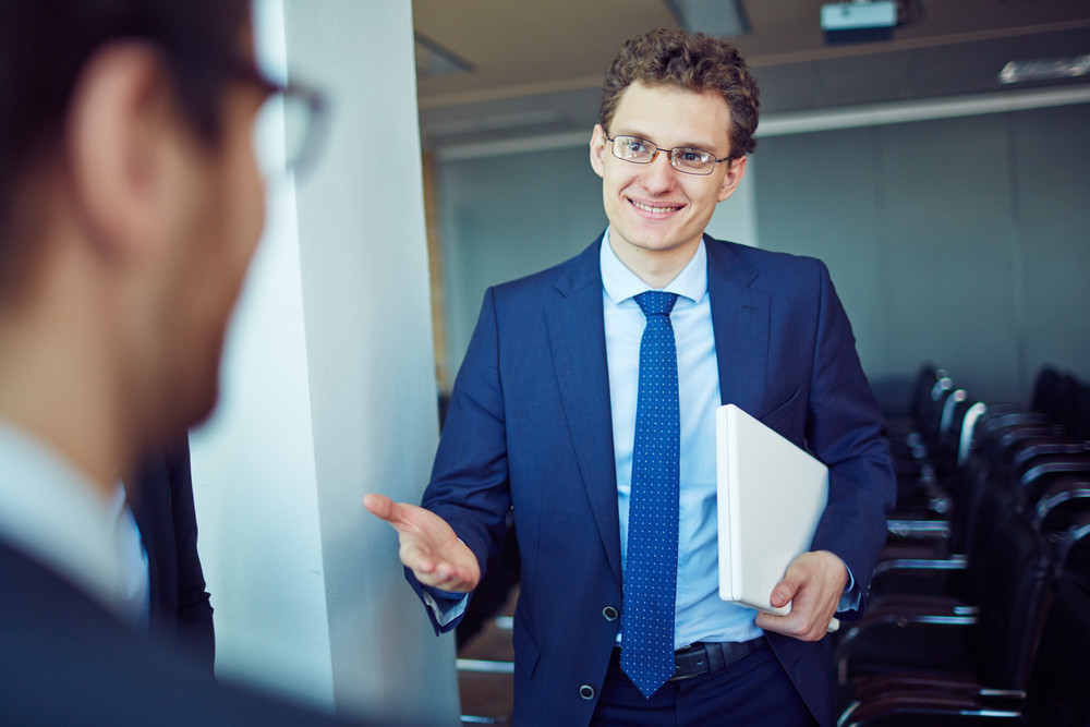 Elegant Employee In Suit And Eyeglasses Welcoming Business Partner