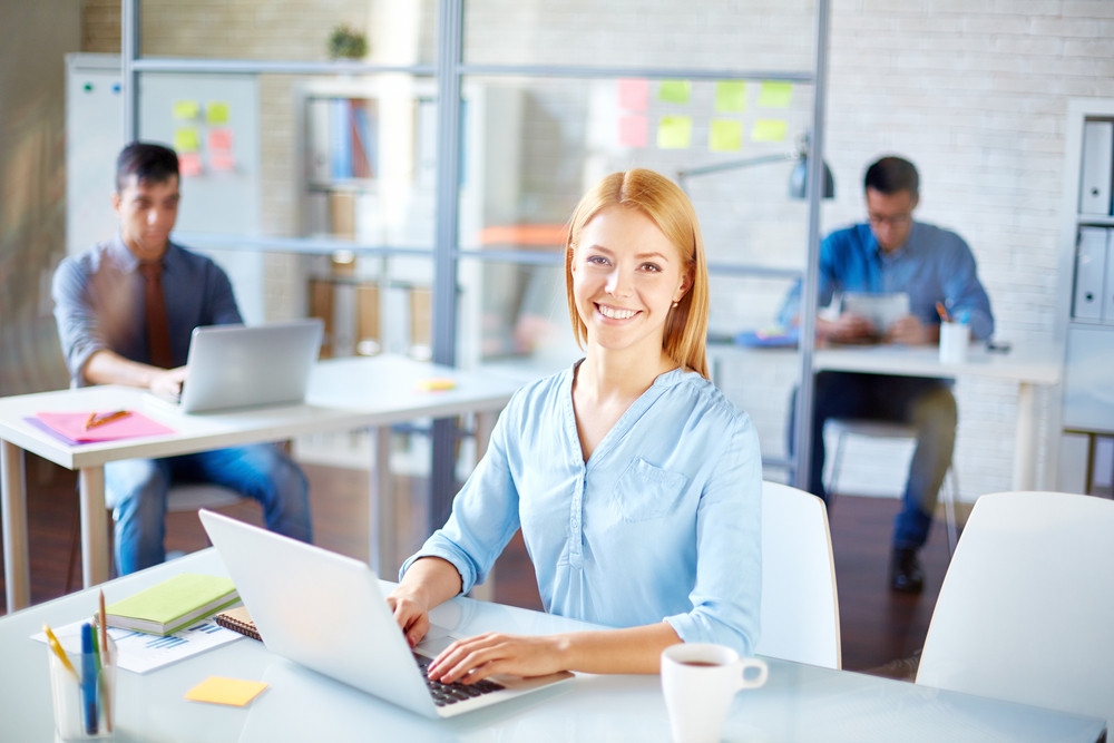 Businesswoman In Casualwear Looking At Camera At Workplace