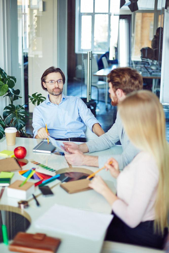 Male Employer Explaining Plans For A Week To Young Employees In Office