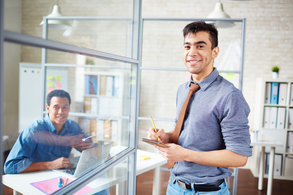 Young Businessman Making Notes In Office