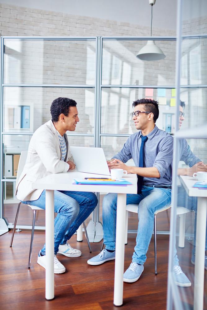 Young Man Talking To Modern Guy While Hiring Him At Work