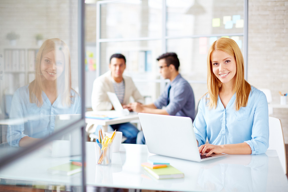 Young Secretary Looking At Camera In Working Environment