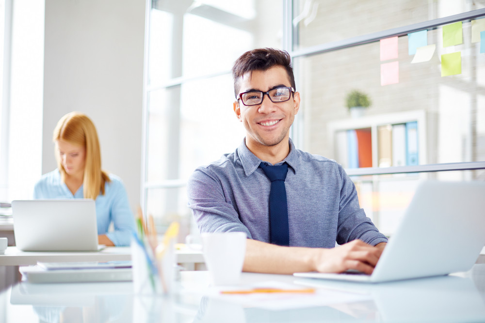 Happy Businessman At Workplace On Background Of His Colleague
