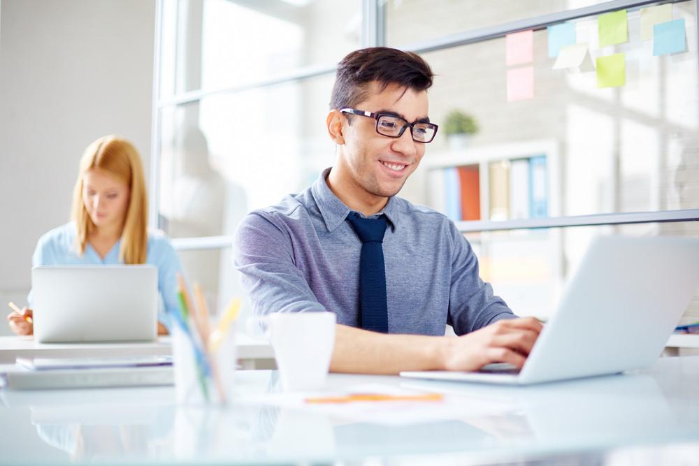 Happy Businessman Computing On Background Of Secretary